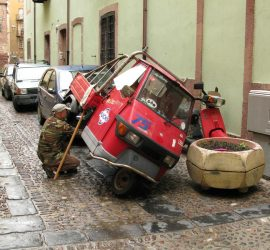 Picture of a Piaggio Ape propped up to be fixed