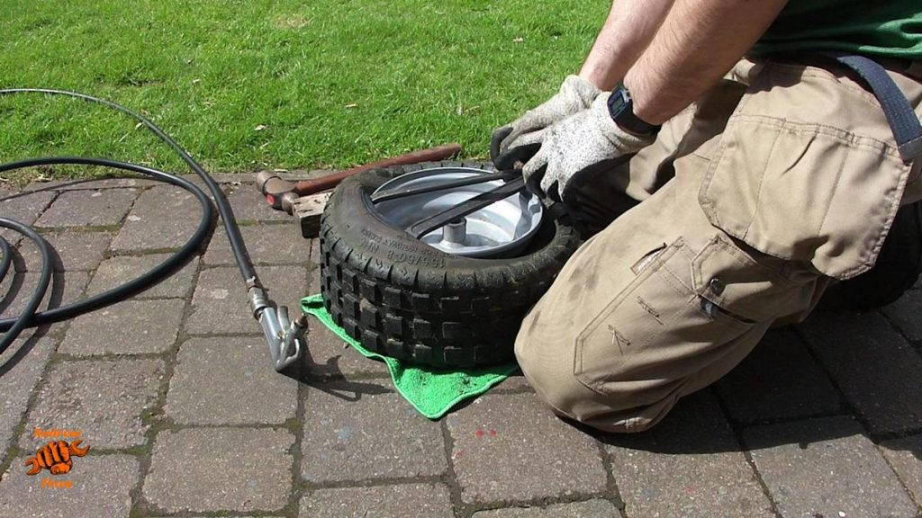 Picture showing tyre levers being used to remove the tyre from the wheel of a Stiga Park 120